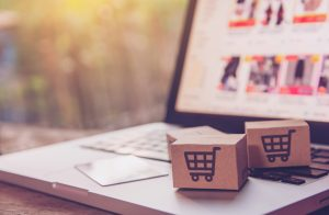 Online shopping - Paper cartons or parcel with a shopping cart logo and credit card on a laptop keyboard. Shopping service on The online web and offers home delivery